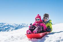 Children Sledding On Snow