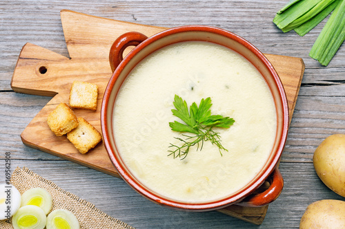 leek and potato soup on wooden cutting board