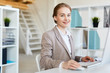 Young successful businesswoman sitting by workplace in office