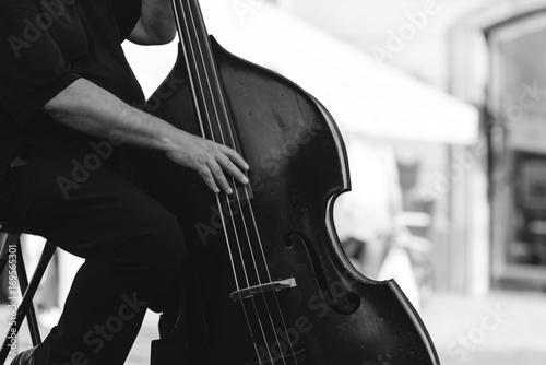 Fototapeta Muzyk grający na kontrabasie na ulicy.
