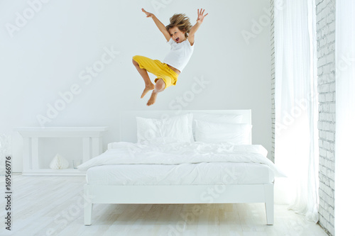 fototapeta na ścianę The child is jumping on the bed