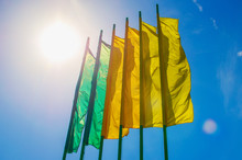 A Row Of Brightly Colored Banners Waving In A Brisk Wind Are Highlighted Against A Blue Sky.
