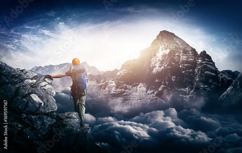 Foto op Plexiglas Alpinisme Bergsteiger an Klettersteig blickt auf fernen Berggipfel am Horizont