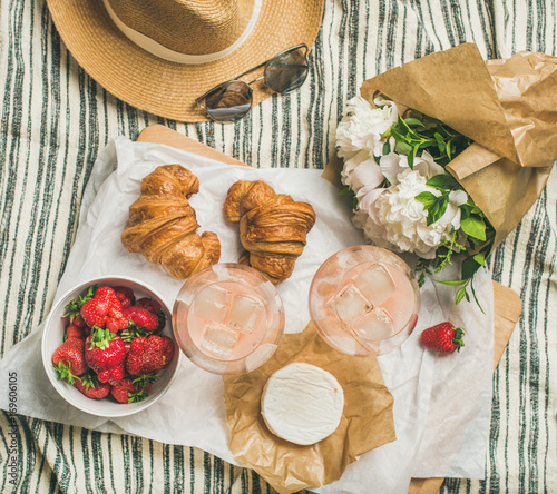 Keuken foto achterwand French style summer outdoor picnic setting. Flat-lay of glasses with rose wine, strawberries, croissants, brie cheese on board, hat, sunglasses, peony flowers, top view. Outdoor gathering concept