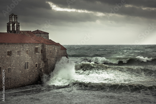Keuken foto achterwand Onweer Dramatic landscape with ancient castle on sea shore during storm with big stormy waves and dramatic sky with rain in fall season on sea coast