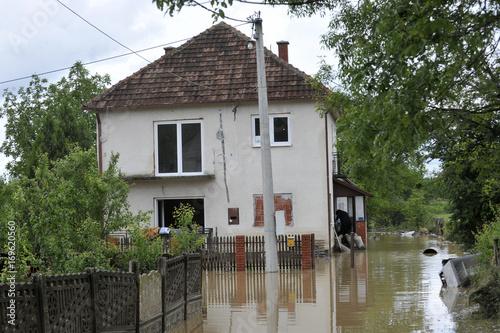 Plakat Konsekwencje powodzi, zalany dom