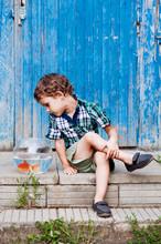 Boy Looking At Fish In Bowl