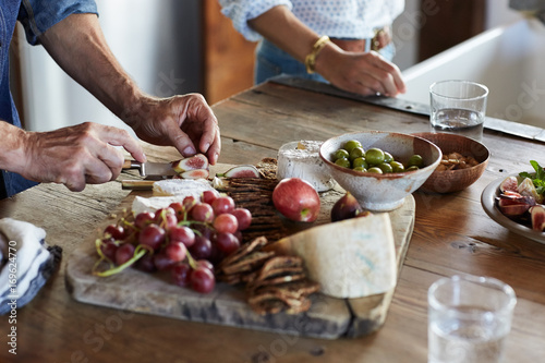 Couple making a cheese plate in the kitchen & Couple making a cheese plate in the kitchen - Buy this stock photo ...