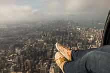 A Woman's Feet Dangle Outside Of A Helicopter As It Flies Over Manhattan.