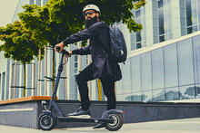 A Man Posing On Electric Scoot...