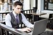 Successful young businessman typing on laptop in cafe