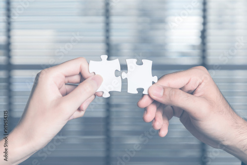 Photo business persons holding pieces of jigsaw puzzle