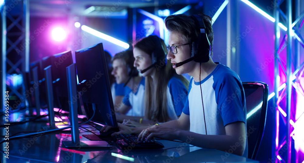 Fototapeta Team of Teenage Gamers Play in Multiplayer PC Video Game on a eSport Tournament. Captain Gives Commands into Microphone, Trying Strategically Win the Game.