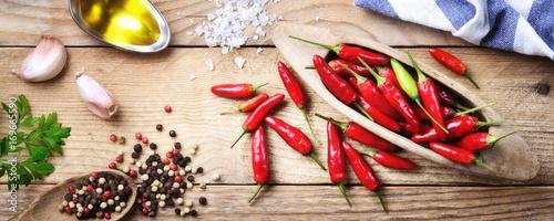 Czerwonego pieprzu chili, pieprzu, pietruszki, czosnku i ekstra dziewiczy oliwa z oliwek na drewnianym tle