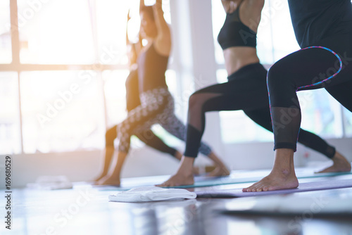 Keuken foto achterwand School de yoga Women exercising in fitness studio yoga classes