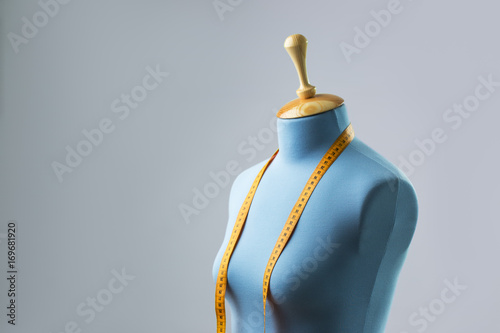 Fotografia, Obraz  Blue tailor dummy with measuring tape alongside the wall.