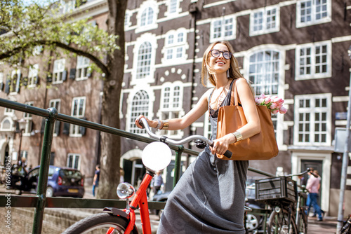 Photo  Young beautiful woman standing with red bicycle and bouguet of tulips on the bri