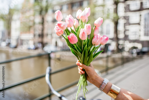 Photo  Holding a bouguet of pink tulips on the water channel and buildings background i