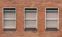 Window Bars And Closed Windows On A Bricks Wall
