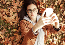 Portrait Of Young Urban Style Woman Lying Down At Park And Taking Image With Smart Phone.Autumn Season.