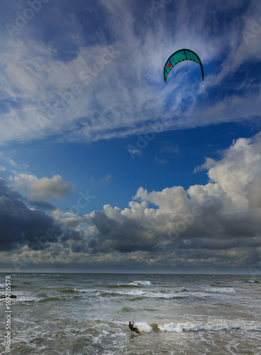 Kitesurfer against blue cloudy sky