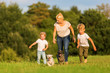 mother with two boys and two dogs runs over a meadow