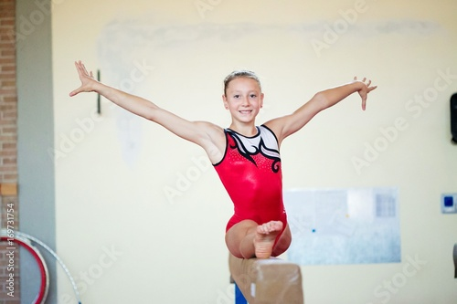 beautiful girl is engaged in sports gymnastics on a log.