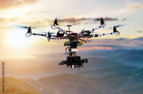 Photo  The drone with the professional cinema camera flying over the misty mountains at sunset