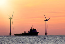 Sustainable Resources. Wind Farm With Ship Silhouette At Tropical Sunrise Or Sunset. Solar And Wind Energy And Food Supply Represented.