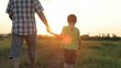 Father and son playing at the sunset time. People having fun outdoors. Concept of friendly family.