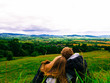A couple relaxing in front of a beautiful countryside scene