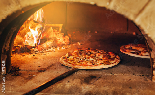 Photo Stands Pizzeria Italian pizza is cooked in a wood-fired oven.