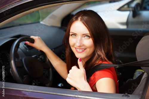 junge Frau mit Dauen hoch im Auto Poster