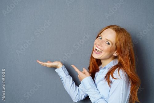 Fotografie, Obraz  lachende frau zeigt mit dem finger auf etwas in ihrer hand