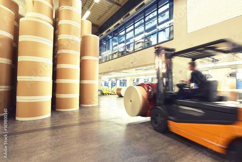 Plakat Wózek widłowy transportuje rolki papieru w magazynie - prędkość nagrywania ruchu // Wózek widłowy transportuje rolki papieru w magazynie w magazynie