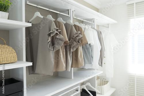 Fotografía  White wardrobe with shirts and pants hanging