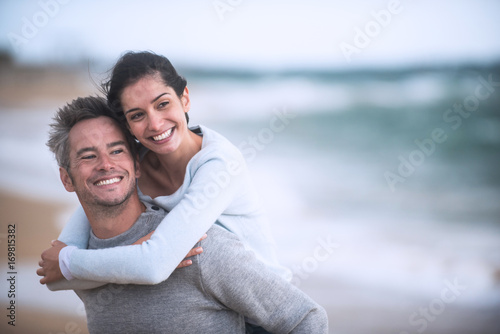 A beautiful couple in their forties  walks on the beach Fototapeta