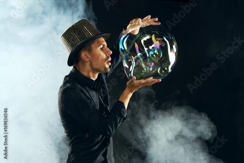 Man artist blowing many soap bubble. Soap bubble show in black studio.