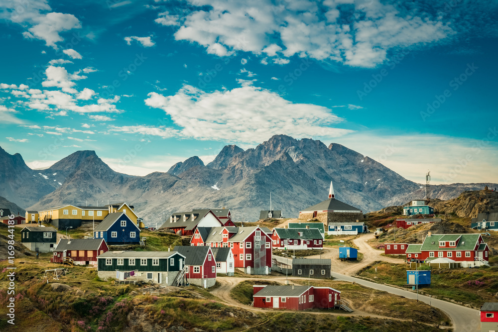 Fototapeta Small town on east coast of Greenland with colorful houses and mountain background