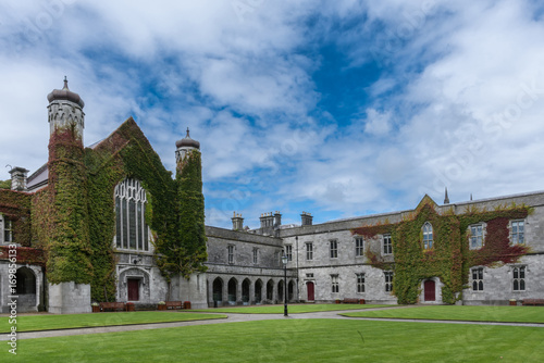 Galway, Ireland - August 5, 2017: Part of historic Quadrangle on National University of Ireland Campus. Quadrangle building covered in Ivy with two towers under blue sky with white clouds. Green lawn.
