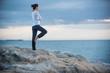 Beautiful woman practicing yoga on the beach at sunrise