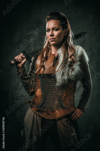Leinwand Poster Viking woman with cold weapon in a traditional warrior clothes