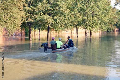 Plakat Ludzie w łodzi motorowej jeżdżą po zalanej ulicy Houston. Konsekwencje huraganu Harvey, Texas, USA