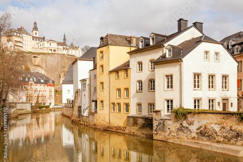 Fotografie, Obraz  Alzette river running through Grund and Ville Haute above, Luxembourg city