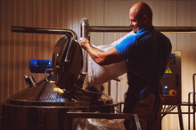Brewer In Brewhouse Pouring Out The Malt To The Tank
