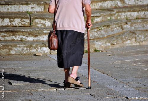 Fotografie, Obraz  Alte, leicht gebückte Frau mit Gehstock und Handtasche allein unterwegs