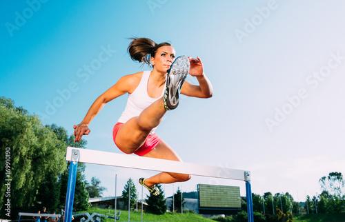 Fotografía  Professional female athlete hurdler running jumping over hurdles