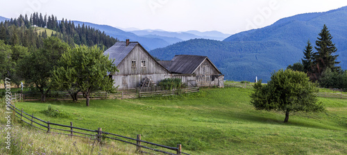 Foto auf Gartenposter Hugel Village houses on hills with green meadows in summer day. House of shepherds in mountains in carpathian