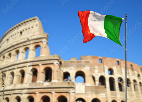 Fényképezés  Italian flag with Flavian Amphitheatre or Colosseum in the background