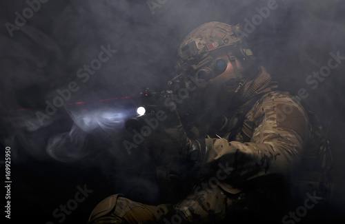 Fotografía  Soldier in military uniform with assault rifle aiming with laser at target in sm